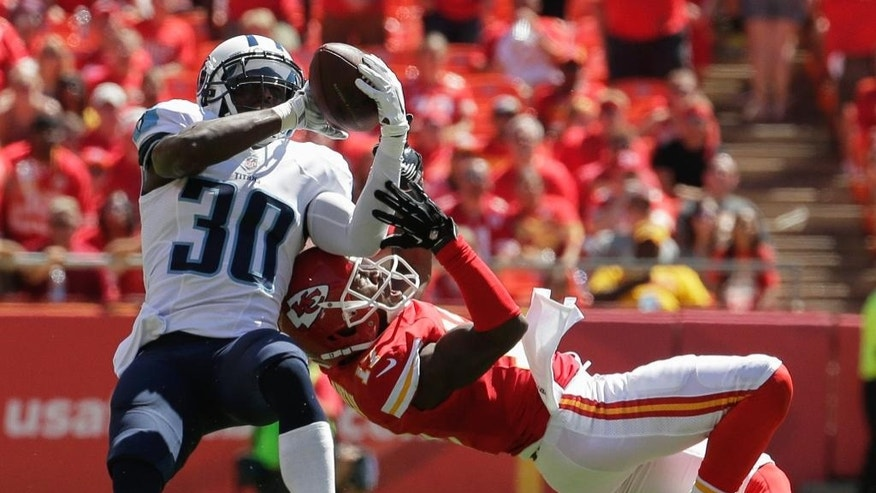 Tennessee Titans cornerback Jason McCourty (30) intercepts a pass intended for Kansas City Chiefs wide receiver Donnie Avery (17) in the first half of an NFL football game in Kansas City, Mo., Sunday, Sept. 7, 2014. (AP Photo/Charlie Riedel)