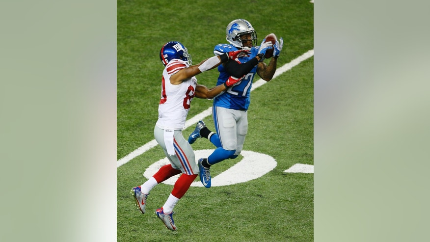 Detroit Lions strong safety Glover Quin (27) intercepts a pass intended for New York Giants wide receiver Victor Cruz (80) during the third quarter of an NFL football game against the in Detroit, Monday, Sept. 8, 2014. (AP Photo/Paul Sancya)