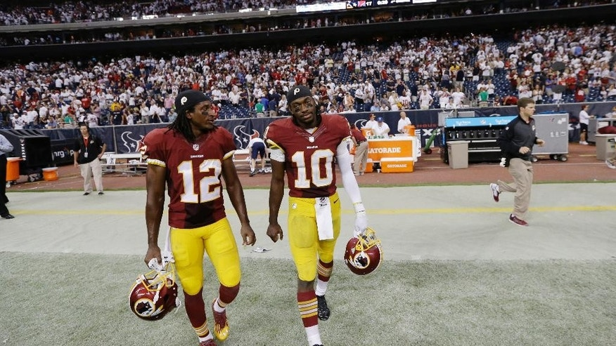 Washington Redskins' Andre Roberts (12) and Robert Griffin III (10) walk off the field after an NFL football game against the Houston Texans, Sunday, Sept. 7, 2014, in Houston. Houston won 17-6. (AP Photo/David J. Phillip)