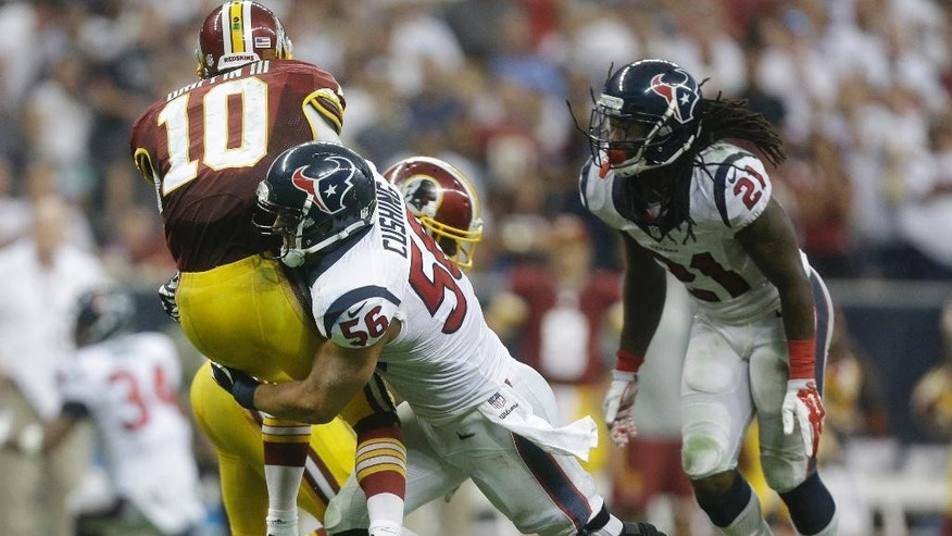 Washington Redskins' Robert Griffin III (10) is hit by Houston Texans' Brian Cushing (56) after releasing a pass during the third quarter of an NFL football game against the Washington Redskins, Sunday, Sept. 7, 2014, in Houston. (AP Photo/Patric Schneider)