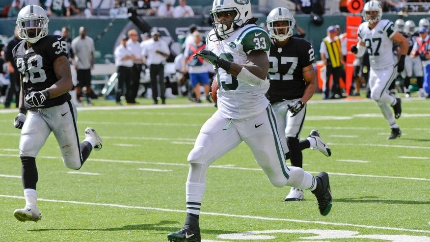 New York Jets running back Chris Ivory (33) rushes past Oakland Raiders' T.J. Carrie (38) and Carlos Rogers (27) for a touchdown during the second half of an NFL football game Sunday, Sept. 7, 2014, in East Rutherford, N.J. (AP Photo/Bill Kostroun)