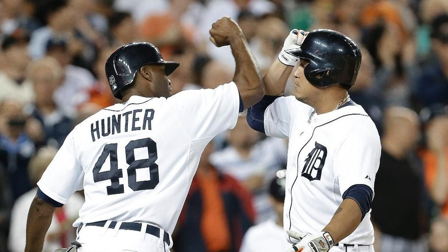 Detroit Tigers' Miguel Cabrera, right, celebrates his two-run home run against the San Francisco Giants with Torii Hunter (48) in the third inning of a baseball game in Detroit Sunday, Sept. 7, 2014. (AP Photo/Paul Sancya)