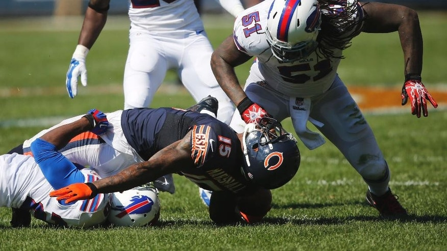 Chicago Bears wide receiver Brandon Marshall (15) is tackled by Buffalo Bills cornerback Corey Graham, left, as linebacker Brandon Spikes (51) looks down on him during the second half of an NFL football game Sunday, Sept. 7, 2014, in Chicago. (AP Photo/Charles Rex Arbogast)