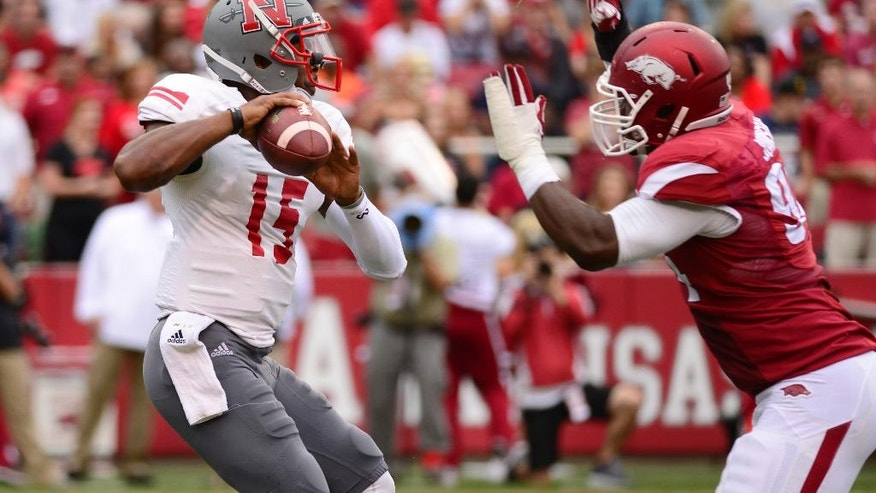Nicholls State quarterback Kalen Henderson (15) looks for a receiver before being sacked by Arkansas defensive tackle Taiwan Johnson, right, in the first quarter of an NCAA college football game in Fayetteville, Ark., Saturday, Sept. 6, 2014. (AP Photo/Sarah Bentham)