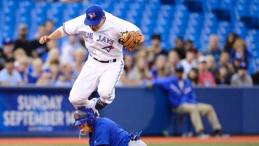 Toronto Blue Jays' Danny Valencia jumps over Chicago Cubs' Javier Baez as Baez steals third base while chewing bubble gum during first inning interleague baseball game action in Toronto on Tuesday, Sept. 9, 2014. (AP Photo/The Canadian Press, Frank Gunn)