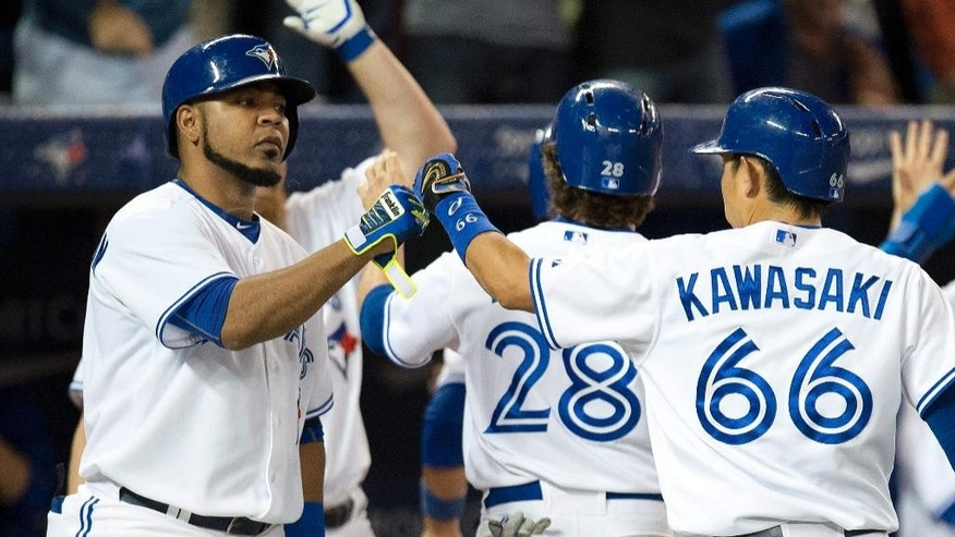 Toronto Blue Jays Edwin Encarnacion (left) congratulates Munenori Kawasaki after he scored on Jose Bautista's three run double during seventh inning action against the Chicago Cubs in Toronto on Tuesday, Sept.9, 2014. (AP Photo/The Canadian Press, Frank Gunn)