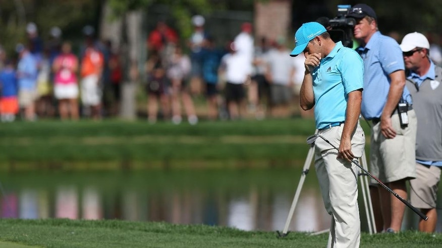 Sergio Garcia, of Spain, reacts after his chip shot off the back of the green on the 17th hole rolled into a water hazard in the final round of the BMW Championship golf tournament in Cherry Hills Village, Colo., on Sunday, Sept. 7, 2014. (AP Photo/David Zalubowski)