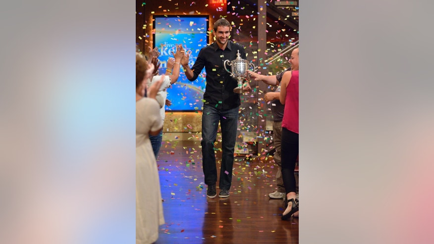 "In this photo provided by Disney-ABC Domestic TV, Marin Cilic, of Croatia, carries his U.S. Open tennis men's singles championship trophy as he is welcomed onto the set of ""LIVE with Kelly and Michael,"" Tuesday, Sept. 9, 2014, in New York. (AP Photo/Disney-ABC Domestic TV, Pawel Kaminski) MANDATORY CREDIT, NO SALES"