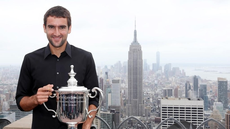 Marin Cilic, of Croatia, poses with the U.S. Open tennis men's singles trophy at the Top of the Rock Observation Deck at Rockefeller Center on Tuesday, Sept. 9, 2014. Cilic defeated Kei Nishikori, of Japan, 6-3, 6-3, 6-3 on Monday. (AP Photo/Mike Groll)