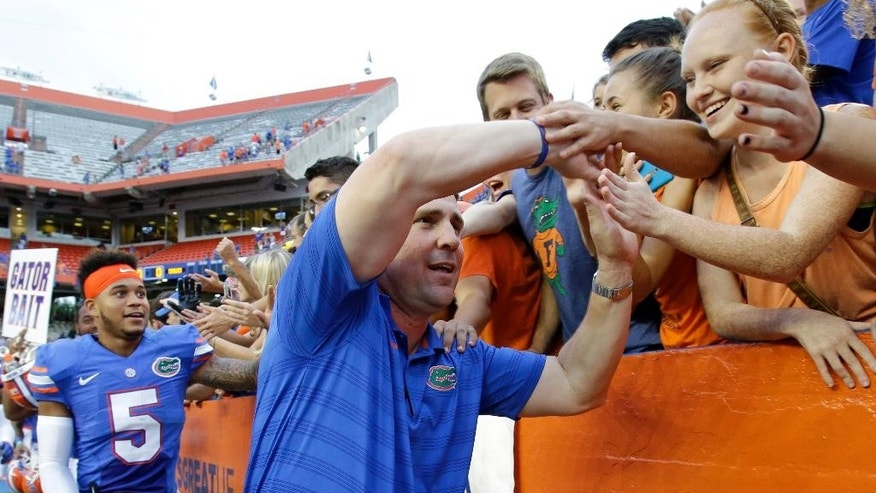 Florida head coach Will Muschamp, right front, and Florida defensive back Jalen Tabor (5) celebrate with fans after defeating Eastern Michigan 65-0 in an NCAA college football game in Gainesville, Fla., Saturday, Sept. 6, 2014. (AP Photo/John Raoux)