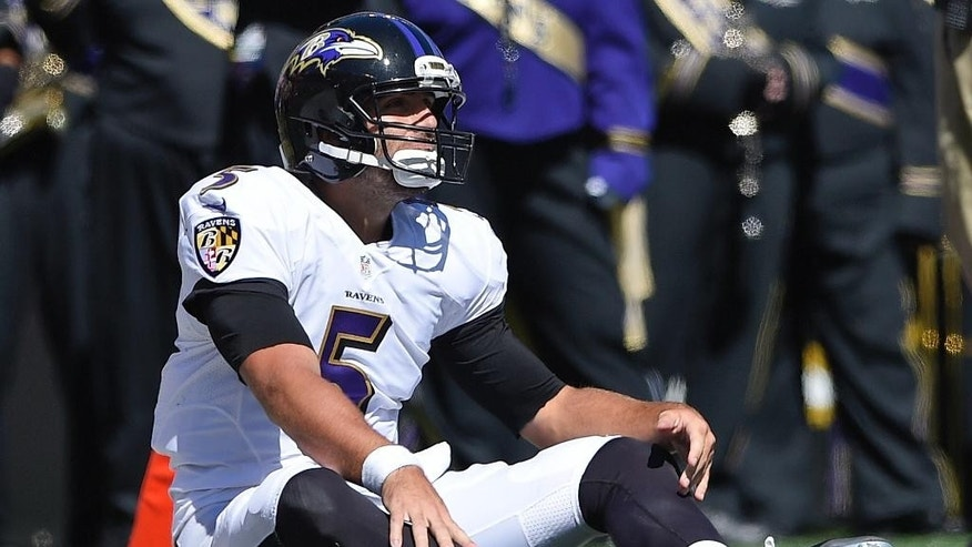Baltimore Ravens quarterback Joe Flacco (5) sits on the turf after the clock runs out in the first half of an NFL football game against the Cincinnati Bengals in Baltimore, Md., Sunday, Sept. 7, 2014. (AP Photo/Nick Wass)