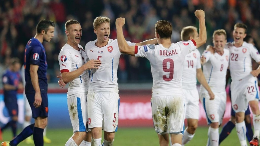 Robin van Persie, left, of the Netherlands walks off the field as Czech Republic players celebrate their victory in the Euro 2016 qualifying match between Czech Republic and Netherlands in Prague, Czech Republic, Tuesday, Sept. 9, 2014.  (AP Photo/Petr David Josek)