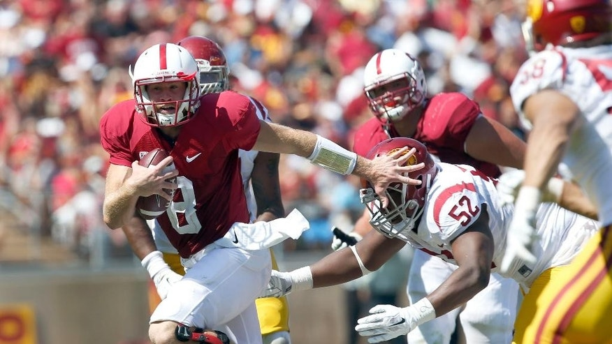 Stanford quarterback Kevin Hogan (8) scrabbles away from Southern California defensive tackle Delvon Simmons (52) during the second half of an NCAA college football game on Saturday, Sept. 6, 2014, in Stanford, Calif. Southern California won 13-10. (AP Photo/Tony Avelar)