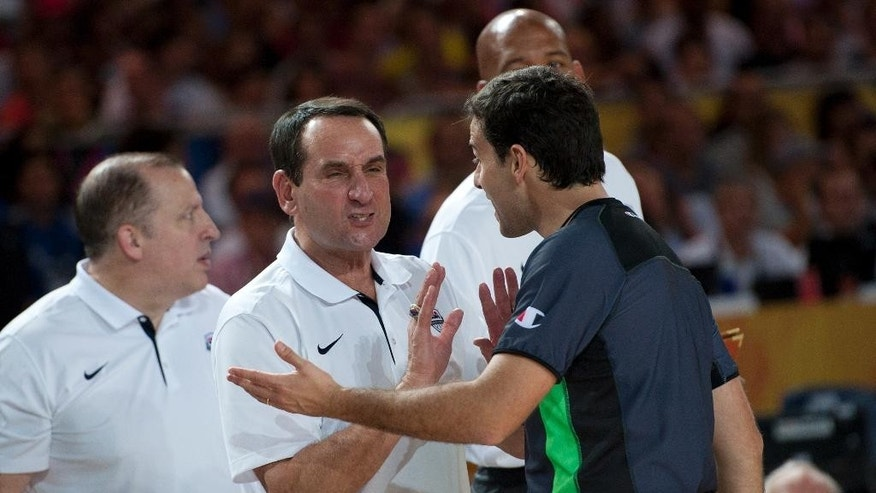 United States coach Mike Krzyzewski, center, talks with the referee during the Group C Basketball World Cup match against Dominican Republic, in Bilbao northern Spain, Wednesday, Sept. 3, 2014. The 2014 Basketball World Cup competition take place in various cities in Spain from Aug. 30 to Sept. 14. (AP Photo/Alvaro Barrientos)