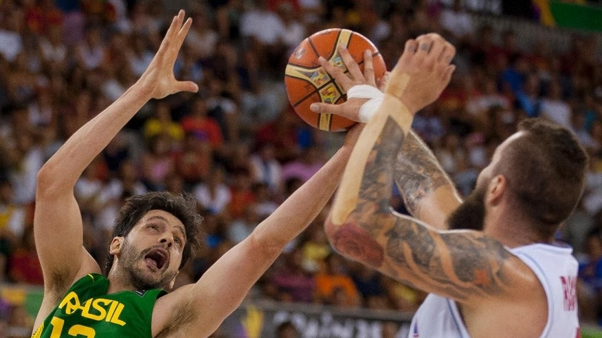Brazil's Guilherme Giovannoni, left, hits a rebound from Serbia's Miroslav Raduljica during the Group A Basketball World Cup match in Granada, Spain, Wednesday, Sept. 3, 2014. The 2014 Basketball World Cup competition will take place in various cities in Spain from Aug. 30 through to Sept. 14. (AP Photo/Daniel Tejedor)