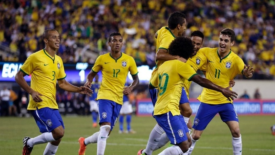 Brazil's Willian (19) celebrates with teammates after scoring against Ecuador during the first half of an international soccer friendly match, Tuesday, Sept. 9, 2014, in East Rutherford, N.J. (AP Photo/Julio Cortez)