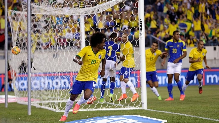 Brazil's Willian (19) celebrates smiles scoring a goal on Ecuador during the first half of an international soccer friendly match, Tuesday, Sept. 9, 2014, in East Rutherford, N.J. (AP Photo/Julio Cortez)