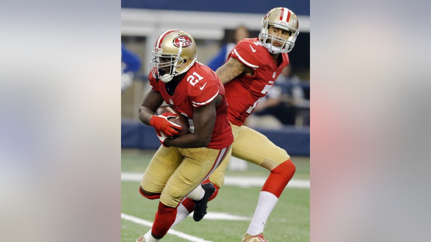 In this Sept. 7, 2014, photo, San Francisco 49ers running back Frank Gore (21) takes the ball from quarterback Colin Kaepernick (7) during the second half of an NFL football game against the Dallas Cowboys in Arlington, Texas. The veteran San Francisco running back reached yet another milestone in Week 1, becoming the 29th player in NFL history to run for 10,000 yards. (AP Photo/LM Otero)