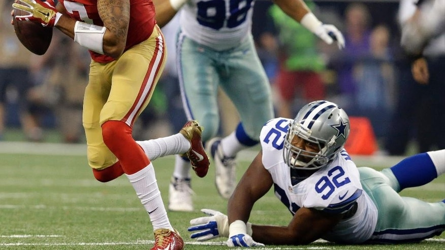 San Francisco 49ers quarterback Colin Kaepernick (7) escapes the grasp of Dallas Cowboys defensive end Jeremy Mincey (92) in the first half of an NFL football game, Sunday, Sept. 7, 2014, in Arlington, Texas. (AP Photo/LM Otero)