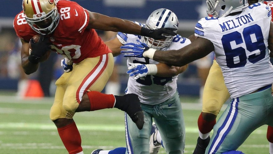 San Francisco 49ers running back Carlos Hyde (28) fights for extra yardage as Dallas Cowboys defensive tackle Henry Melton (69) and Tyrone Crawford (98) attempt the stop during the second half of an NFL football game, Sunday, Sept. 7, 2014, in Arlington, Texas. (AP Photo/LM Otero)