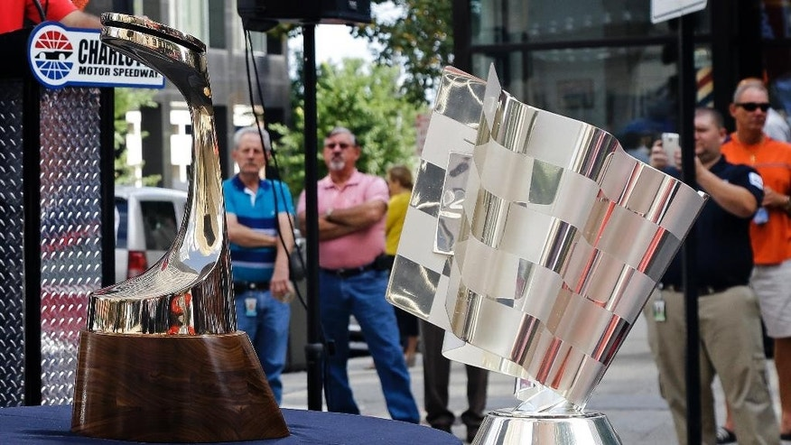 Onlookers look at the Bank of America 500 trophy, left, and the Chase for the NASCAR Sprint Cup trophy during a trophy tour event in Raleigh, N.C., Wednesday, Sept. 10, 2014. (AP Photo/Gerry Broome)