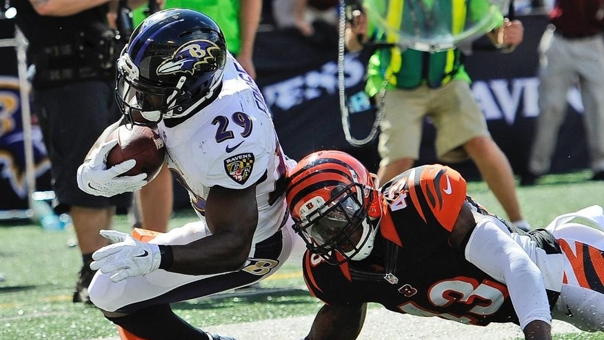 Baltimore Ravens running back Justin Forsett (29) scores a touchdown under pressure form Cincinnati Bengals strong safety George Iloka (43) during the second half of an NFL football game in Baltimore, Md., Sunday, Sept. 7, 2014. (AP Photo/Nick Wass)