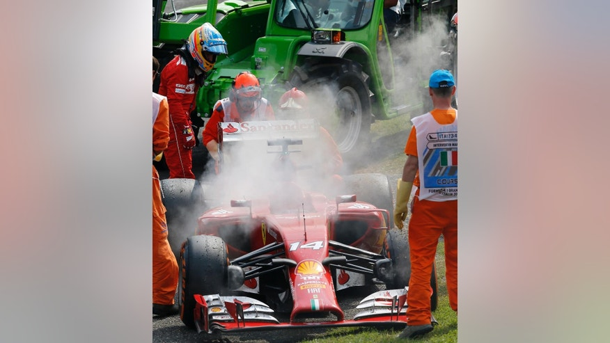 Ferrari driver Fernando Alonso of Spain watches his car after failing to complete the Italian Formula One Grand Prix at the Monza racetrack, in Monza, Italy, Sunday, Sept. 7, 2014. (AP Photo/Antonio Calanni)