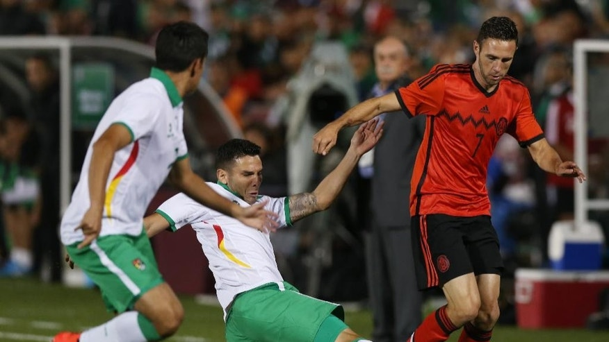 Mexico defenseman Miguel Layun, right, has ball kicked away by Bolivia midfielder Alejandro Melean, center, as defenseman Ronald Eguino defends during the first half of an international friendly soccer game in Commerce City, Colo., on Tuesday, Sept. 9, 2014. (AP Photo/David Zalubowski)