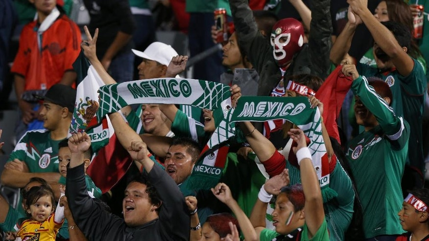 Fans cheer for Mexico as they face Bolivia in the first half of an international friendly soccer game in Commerce City, Colo., on Tuesday, Sept. 9, 2014. (AP Photo/David Zalubowski)