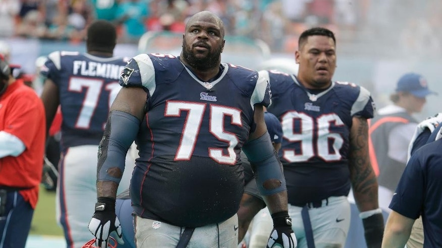 New England Patriots defensive tackle Vince Wilfork (75) looks up at the scoreboard after the Miami Dolphins scored in the second half of an NFL football game, Sunday, Sept. 7, 2014, in Miami Gardens, Fla. The Dolphins defeated the Patriots 33-20. At right is defensive tackle Sealver Siliga (96). (AP Photo/Lynne Sladky)