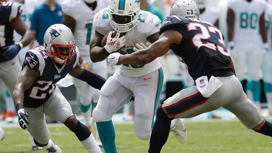 New England Patriots cornerback Darrelle Revis (24) and  free safety Patrick Chung (23) attempt to tackle Miami Dolphins running back Knowshon Moreno (28) during the second half of an NFL  football game, in Miami Gardens, Fla., Sunday Sept. 7, 2014. The Dolphins defeated the Patriots 33-20. (AP PhotoLynne Sladky)