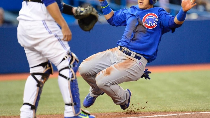 Toronto Blue Jays catcher Dioner Navarro looks on as as Chicago Cubs' Javier Baez scores on a Cubs' Jorge Soler sacrifice fly to center during first inning interleague baseball game action in Toronto on Tuesday, Sept. 9, 2014. (AP Photo/The Canadian Press, Frank Gunn)