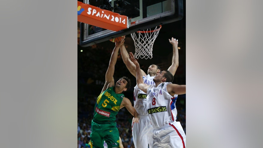 Serbia's Nenad Krstic, center, and Nemanja Bjelica, right, get up to block a shot by Brazil's Raulzinho Neto during the basketball World Cup quarter finals match between Serbia and Brazil in Madrid, Spain, Wednesday, Sept. 10, 2014. The 2014 Basketball World Cup competition will take place in various cities in Spain from Aug. 30 through to Sept. 14. (AP Photo/Daniel Ochoa de Olza)