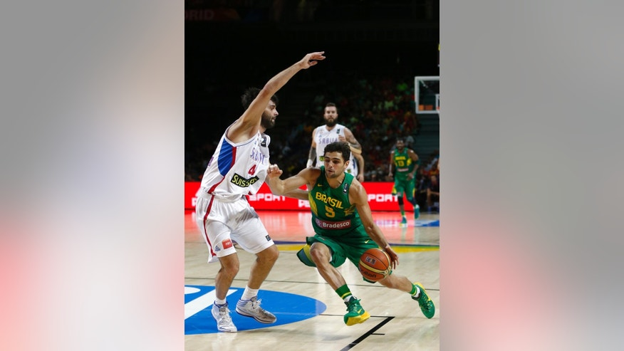 Brazil's Raulzinho Neto, right, drives around Serbia's Milos Teodosic during the basketball World Cup quarter finals match between Serbia and Brazil in Madrid, Spain, Wednesday, Sept. 10, 2014. The 2014 Basketball World Cup competition will take place in various cities in Spain from Aug. 30 through to Sept. 14. (AP Photo/Daniel Ochoa de Olza)