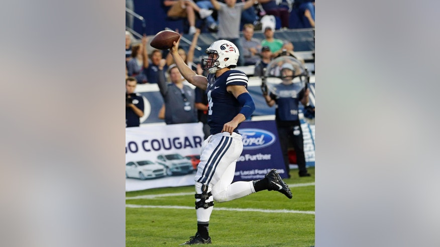 FILE In this Sept. 11, 2014, file photo, BYU quarterback Taysom Hill celebrates after scoring against Houston in the first quarter of an NCAA college football game in Provo, Utah. Hill has made a career of such plays, where he tucks the ball, puts his head down and fearlessly plows downfield. ``Whatever it takes,'' he says. (AP Photo/Rick Bowmer, File)