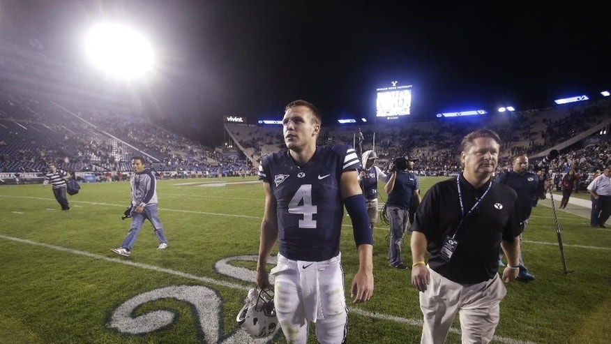 BYU quarterback Taysom Hill (4) walks off the field after an NCAA college football game against Houston on Thursday, Sept. 11, 2014, in Provo, Utah. BYU won 33-25. (AP Photo/Rick Bowmer)