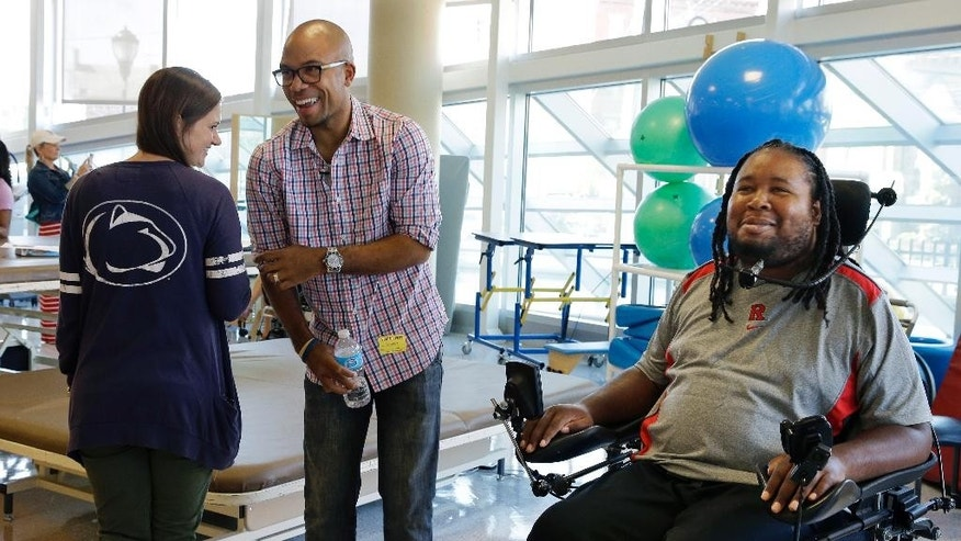 Eric LeGrand, right, alumni of Rutgers University and Adam Taliaferro, center, alumni of Penn State University, college football players who suffered serious spinal cord injuries on the field, react as child life specialist Tara Mohamed shows her Penn State shirt while visiting children at PSE&G Children's Specialized Hospital, Wednesday, Sept. 10, 2014, in New Brunswick, N.J. LeGrand and Taliaferro will be the honorary captains when Rutgers and Penn State meet Saturday at High Point Solutions Stadium in the Big Ten Conference opener. (AP Photo/Mel Evans)