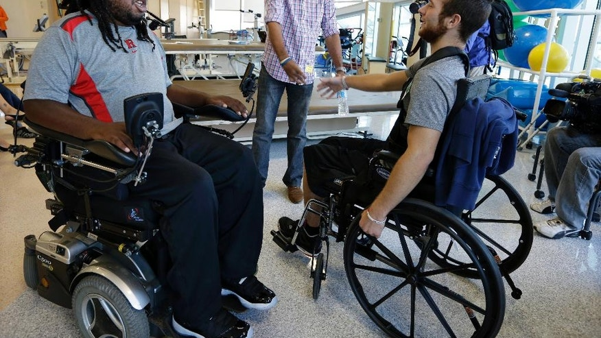 Eric LeGrand, left, alumni of Rutgers University and Adam Taliaferro, center, alumni of Penn State University, college football players who suffered serious spinal cord injuries on the field, talk with  Jonathan Ulassin, 19, while visiting children at PSE&G Children's Specialized Hospital,  Wednesday, Sept. 10, 2014, in New Brunswick, N.J. LeGrand and Taliaferro will be the honorary captains when Rutgers and Penn State meet Saturday at High Point Solutions Stadium in the Big Ten Conference opener. (AP Photo/Mel Evans)