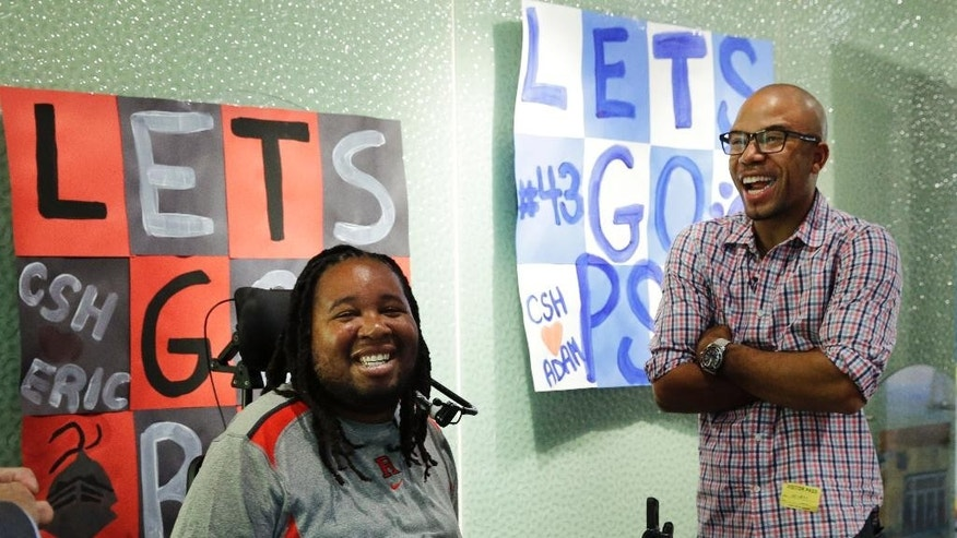 Eric LeGrand, left, alumni of Rutgers University and Adam Taliaferro alumni of Penn State University, college football players who suffered serious spinal cord injuries on the field, laugh as they stand near posters before visiting children at PSE&G Children's Specialized Hospital, Wednesday, Sept. 10, 2014, in New Brunswick, N.J. LeGrand and Taliaferro will be the honorary captains when Rutgers and Penn State meet Saturday at High Point Solutions Stadium in the Big Ten Conference opener. (AP Photo/Mel Evans)