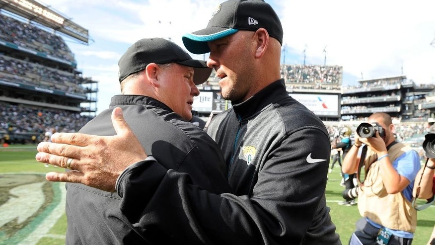Philadelphia Eagles head coach Chip Kelly, left, and Jacksonville Jaguars head coach Gus Bradley meet after an NFL football game, Sunday, Sept. 7, 2014, in Philadelphia. Philadelphia won 34-17.  (AP Photo/Michael Perez)