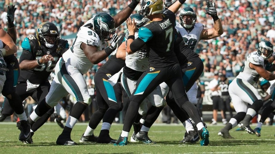 Jacksonville Jaguars quarterback Chad Henne, right, tries to get the pass off before getting hit by Philadelphia Eagles defensive end Fletcher Cox, left, during the second half of an NFL football game, Sunday, Sept. 7, 2014, in Philadelphia. The Eagles won 34-17. (AP Photo/Chris Szagola)