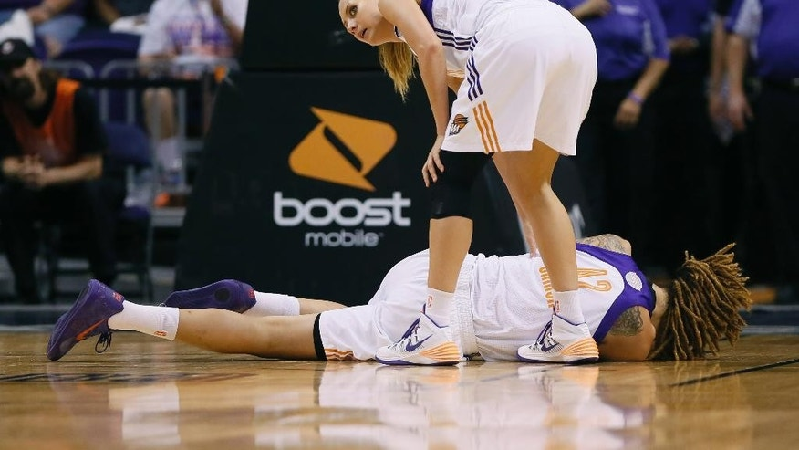 Phoenix Mercury forward Penny Taylor stands over center Brittney Griner (42) after Griner got a cut above her eye during the first half of  Game 2 of the WNBA basketball finals against the Chicago Sky, Tuesday, Sept. 9, 2014, in Phoenix. (AP Photo/Matt York)
