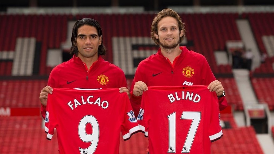 Manchester United's new players Radamel Falcao, left,  and Daley Blind pose for photographs at Old Trafford Stadium, Manchester, England, Thursday Sept. 11, 2014. The Colombian striker Falcao joined on a season-long loan deal from Ligue 1 side Monaco and Blind signed from Ajax as Louis van Gaal looks to bolster his attacking options. (AP Photo/Jon Super)