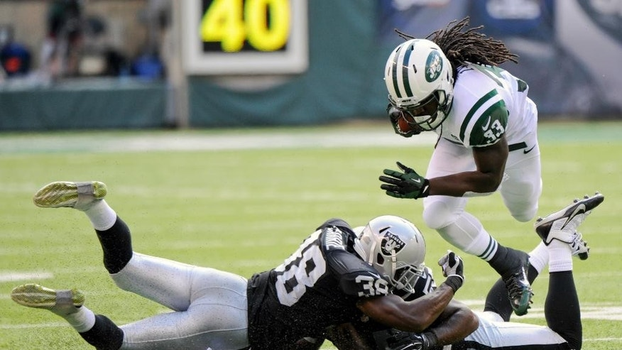 New York Jets' Chris Ivory (33) avoids being tackled by Oakland Raiders' T.J. Carrie (38) and Sio Moore (55) during the first half of an NFL football game Sunday, Sept. 7, 2014, in East Rutherford, N.J. (AP Photo/Bill Kostroun)