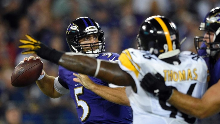 Baltimore Ravens quarterback Joe Flacco (5) looks to pass under pressure from Pittsburgh Steelers nose tackle Cam Thomas (96) during the first half of an NFL football game Thursday, Sept. 11, 2014, in Baltimore. (AP Photo/Nick Wass)