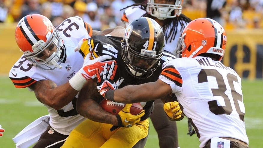 Pittsburgh Steelers' Antwon Blake (41) is tackled by Cleveland Browns cornerback Jordan Poyer (33) and defensive back K'Waun Williams (36) after making a first down on a fake punt attempt in the fourth quarter of the NFL football game on Sunday, Sept. 7, 2014 in Pittsburgh. (AP Photo/Don Wright)