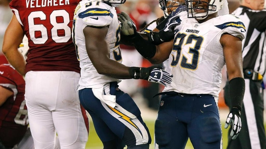 San Diego Chargers outside linebacker Dwight Freeney (93) celebrates a stop against the Arizona Cardinals with teammate Jeremiah Attaochu (97) during the second half of an NFL football game, Monday, Sept. 8, 2014, in Glendale, Ariz. (AP Photo/Ross D. Franklin)