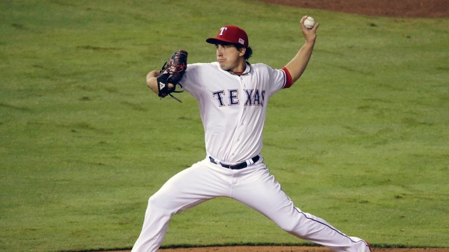 Texas Rangers starting pitcher Derek Holland works against the Atlanta Braves in the fifth inning of a baseball game, Friday, Sept. 12, 2014, in Arlington, Texas. (AP Photo/Tony Gutierrez)