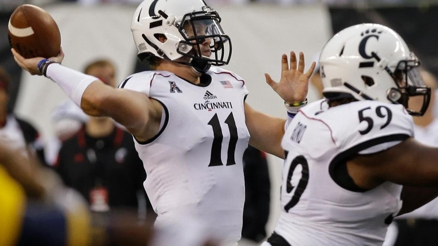 Cincinnati quarterback Gunner Kiel (11) throws a 22-yard touchdown pass in the first half of an NCAA college football game against Toledo, Friday, Sept. 12, 2014, in Cincinnati. (AP Photo/Al Behrman)
