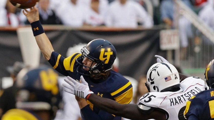 Toledo quarterback Logan Woodside passes under pressure from Cincinnati defensive end Terrell Hartsfield in the first half of an NCAA college football game, Friday, Sept. 12, 2014, in Cincinnati. (AP Photo/Al Behrman)